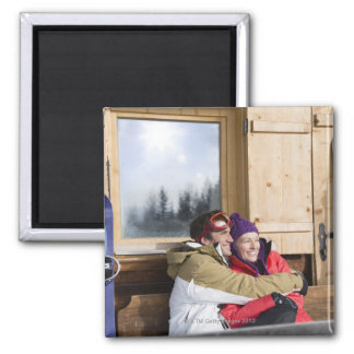 Mid adult couple embracing outside log cabin magnets