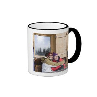 Mid adult couple embracing outside log cabin ringer coffee mug