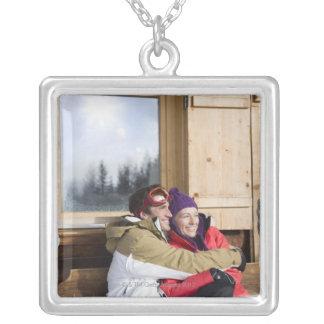Mid adult couple embracing outside log cabin pendant