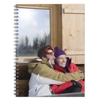 Mid adult couple embracing outside log cabin note books
