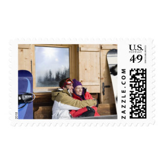 Mid adult couple embracing outside log cabin stamps