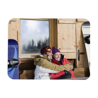 Mid adult couple embracing outside log cabin flexible magnet