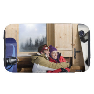 Mid adult couple embracing outside log cabin tough iPhone 3 cover