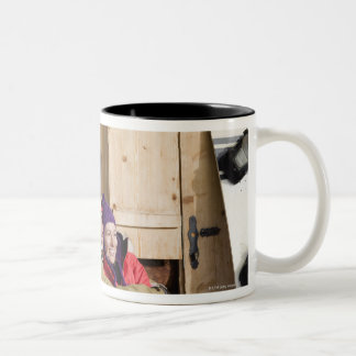 Mid adult couple embracing outside log cabin Two-Tone coffee mug
