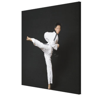 Mid adult man performing the side kick canvas print