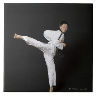 Mid adult man performing the side kick ceramic tile