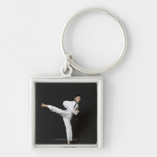 Mid adult man performing the side kick keychain