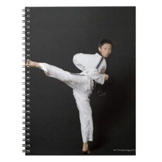 Mid adult man performing the side kick spiral notebooks