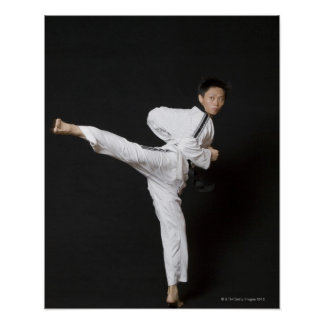 Mid adult man performing the side kick poster