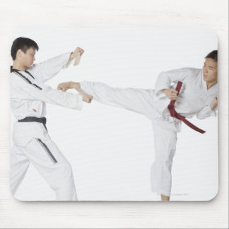 Mid adult man practicing kickboxing with a young mouse pad