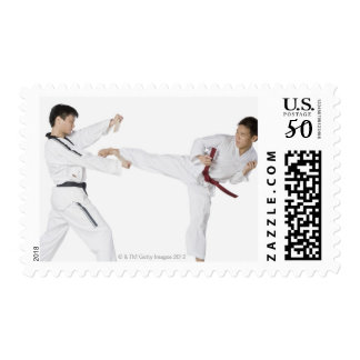 Mid adult man practicing kickboxing with a young postage