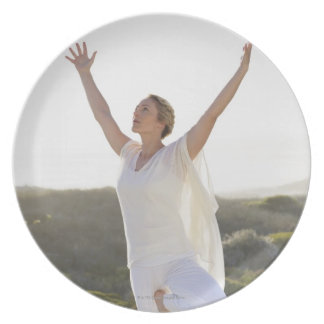 Mid adult woman practicing yoga 2 dinner plate