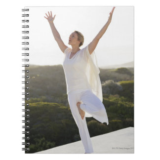 Mid adult woman practicing yoga 2 spiral notebook