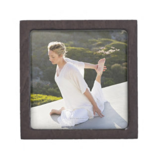 Mid adult woman practicing yoga exercise at gift box