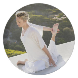 Mid adult woman practicing yoga exercise at melamine plate