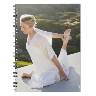 Mid adult woman practicing yoga exercise at notebooks