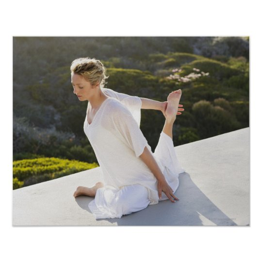 Mid adult woman practicing yoga exercise at poster
