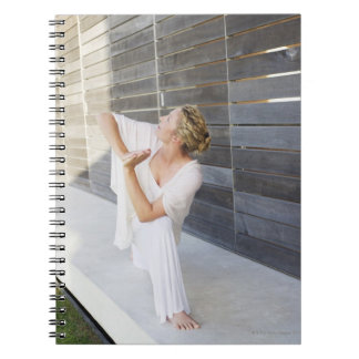 Mid adult woman practicing yoga notebook