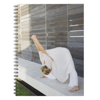 Mid adult woman stretching her arms spiral note book