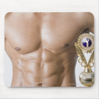 Mid section view of a young man holding a trophy mouse pad