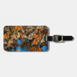 Migrating monarch butterflies cling to leaves luggage tag