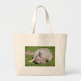 Minipig sleeping on grass large tote bag