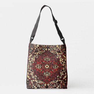 Mirada de la alfombra persa en rojo oscuro y poner bolsa cruzada