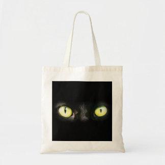 Mirada fija de los ojos de gato del negro y del a bolsa