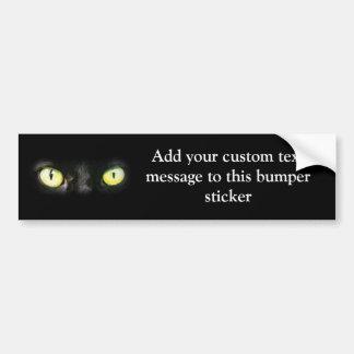 Mirada fija de los ojos de gato, del negro y del a pegatina para auto