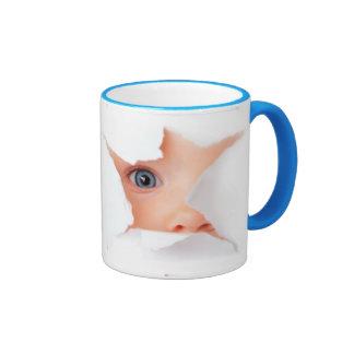 Mirando a escondidas al bebé le ve taza de dos colores