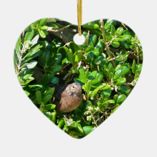 Mirlo en un arbusto del laurel adorno navideño de cerámica en forma de corazón