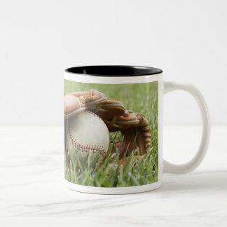 Mitón de béisbol con la bola en hierba tazas de café