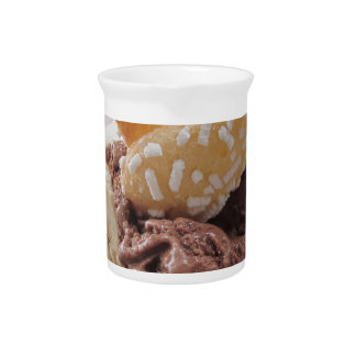 Mixed ice cream scoops with biscuits in bowl pitcher