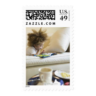 Mixed race boy reading book on sofa postage