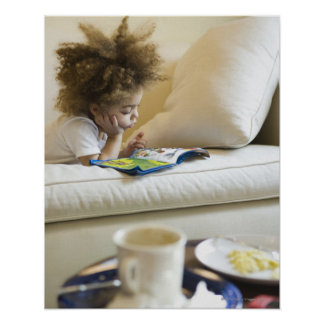 Mixed race boy reading book on sofa print