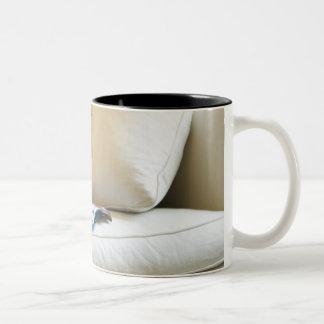 Mixed race boy reading book on sofa Two-Tone coffee mug