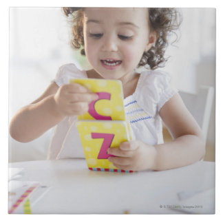 Mixed race girl playing with alphabet cards ceramic tile