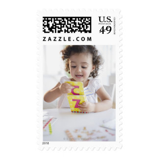 Mixed race girl playing with alphabet cards postage
