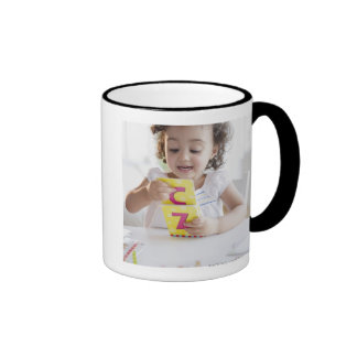 Mixed race girl playing with alphabet cards ringer mug