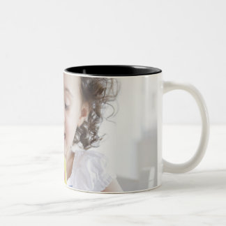Mixed race girl playing with alphabet cards Two-Tone coffee mug