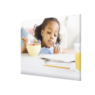 Mixed race girl reading and eating breakfast canvas print