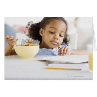 Mixed race girl reading and eating breakfast greeting cards