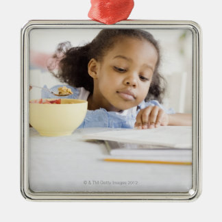 Mixed race girl reading and eating breakfast metal ornament
