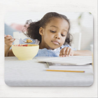 Mixed race girl reading and eating breakfast mouse pad
