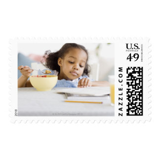 Mixed race girl reading and eating breakfast postage stamps
