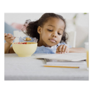 Mixed race girl reading and eating breakfast posters