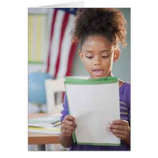 Mixed race girl reading report at school greeting cards