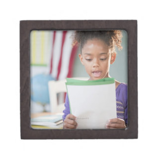 Mixed race girl reading report at school keepsake box