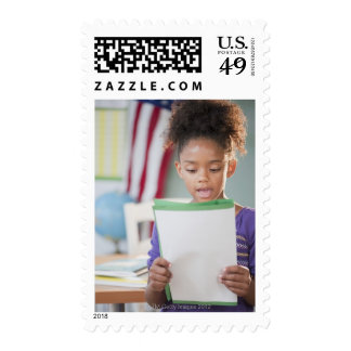 Mixed race girl reading report at school stamps