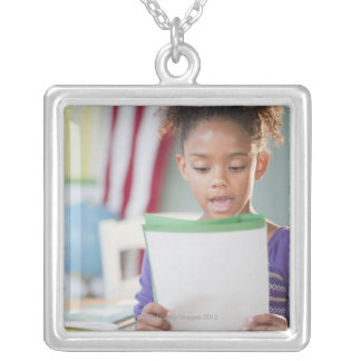 Mixed race girl reading report at school silver plated necklace